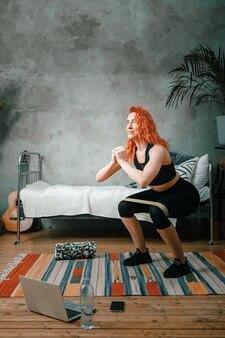 A jovem pratica esportes em casa. atleta alegre com cabelo ruivo agacha no quarto com elásticos de fitness esportivo