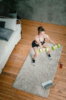 A jovem pratica esportes em casa