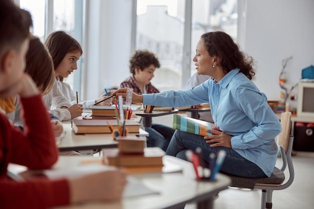 A jovem professora ajuda a ler seu aluno. crianças do ensino fundamental sentadas em mesas e lendo livros em sala de aula.