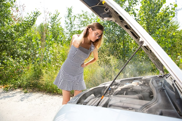 A jovem quebrou o carro enquanto viajava para descansar. ela está tentando consertar o quebrado sozinha ou deveria pedir carona. ficando nervoso. fim de semana, problemas na estrada, férias.