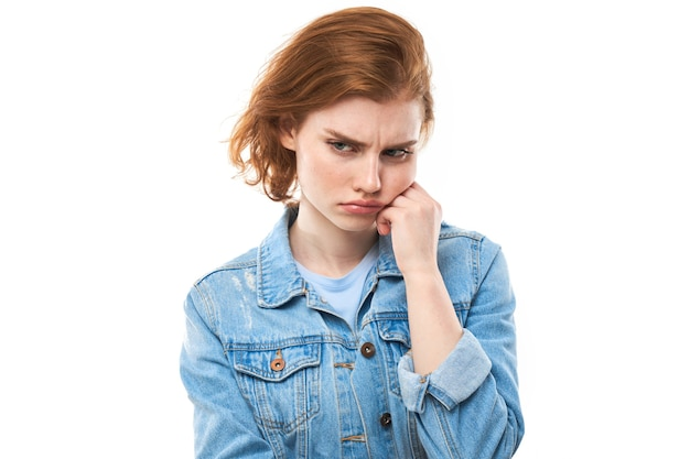 A jovem ruiva ponderou. ressentimento e decepção. modelo de menina com uma jaqueta jeans azul sobre fundo branco. estou com dor de dentes