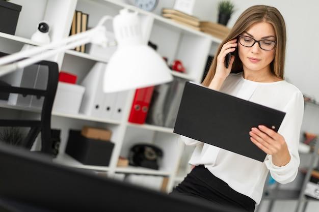 A jovem se sentou na mesa do escritório, segurando um tablet com lençóis na mão