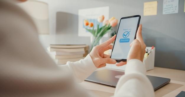 A jovem senhora asiática usa um produto de compra on-line de pedido de celular e paga contas com aplicativo bancário com transação bem-sucedida. ficar em casa, atividade de quarentena, atividade lúdica para prevenção do coronavírus.