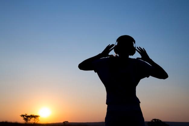 A jovem silhueta com fone de ouvido ao pôr do sol