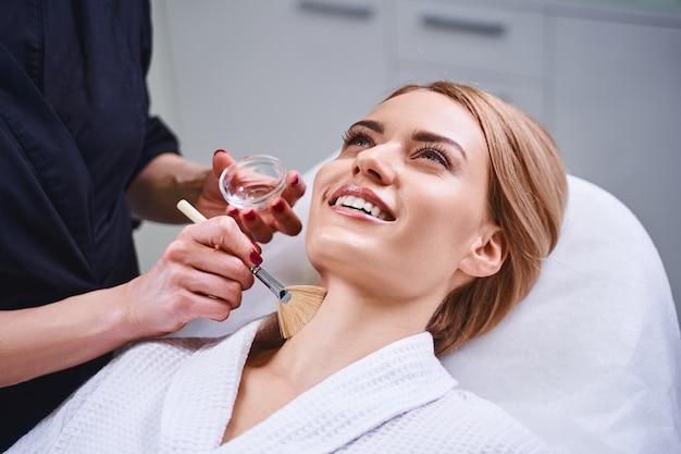 A jovem sorridente está aproveitando a visita ao salão de beleza e aguardando os procedimentos do especialista
