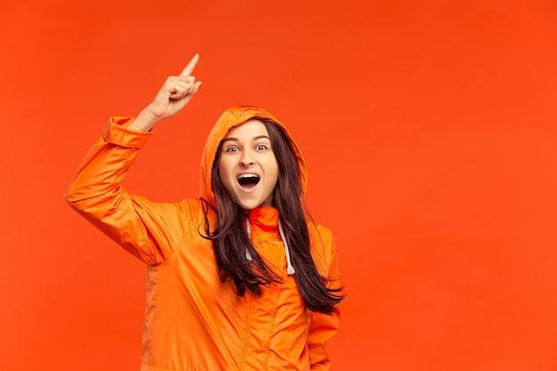 A jovem sorridente feliz posando no estúdio em outono casaco laranja apontando para cima isolado no vermelho. emoções positivas humanas. conceito de clima frio. conceitos de moda feminina