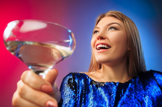 A jovem surpreendida em roupas de festa, posando com copo de vinho