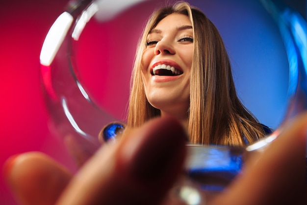 A jovem surpresa em roupas de festa, posando com um copo de vinho.