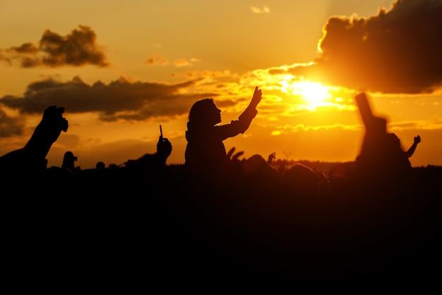 A jovem tira fotos do festival em seu smartphone. silhueta negra sobre o pôr do sol.