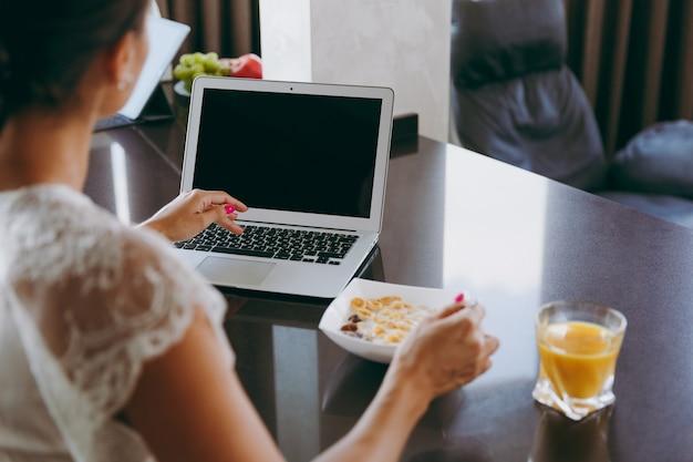 A jovem trabalhando com um laptop enquanto o café da manhã com cereais e leite