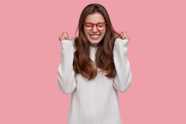 A jovem triunfante de joful fecha os punhos em gesto de vitória, sorri amplamente de satisfação, alegra-se com a vitória, tem longos cabelos escuros