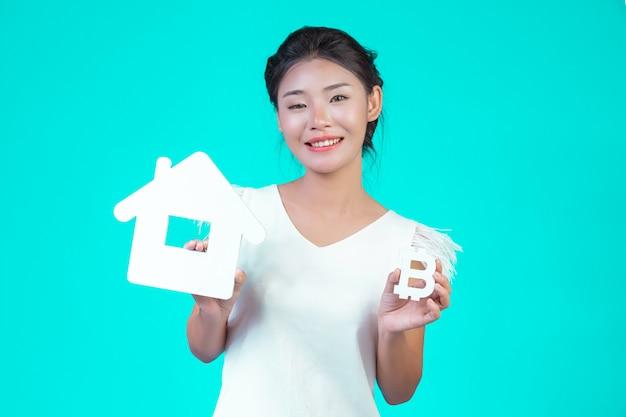 A jovem usava uma camisa branca de mangas compridas com padrão floral, segurando o símbolo da casa e o símbolo da moeda com um azul.