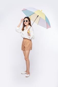 A jovem vestia camisa branca e bermuda, chapéu, óculos e guarda-chuva