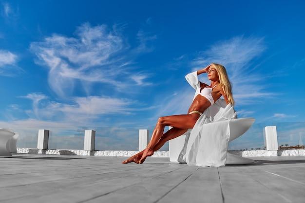 A jovem vestida de branco em um terraço e céu azul