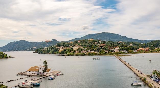 A lagoa halkiopoulos com o mosteiro vlacherna e pontikonisi significa a ilha do rato em corfu, grécia. bela paisagem da praia do mar jônico.