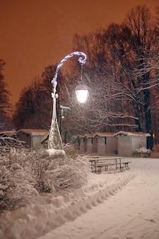 A lâmpada da rua brilha em um parque noturno com muita neve no inverno