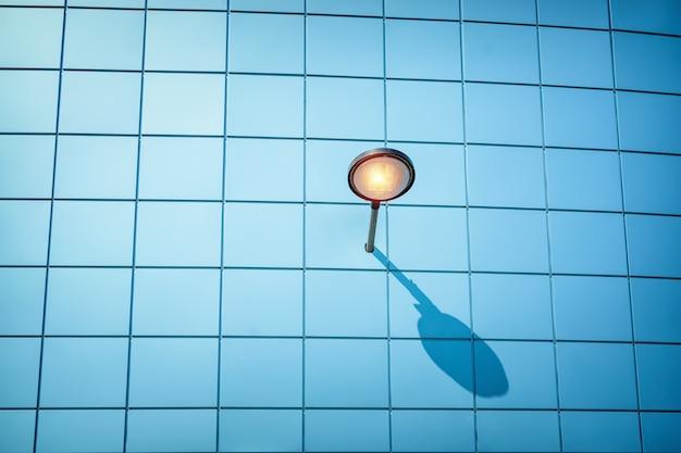 A lâmpada de rua joga a sombra sobre a parede azul. minimalismo de conceito
