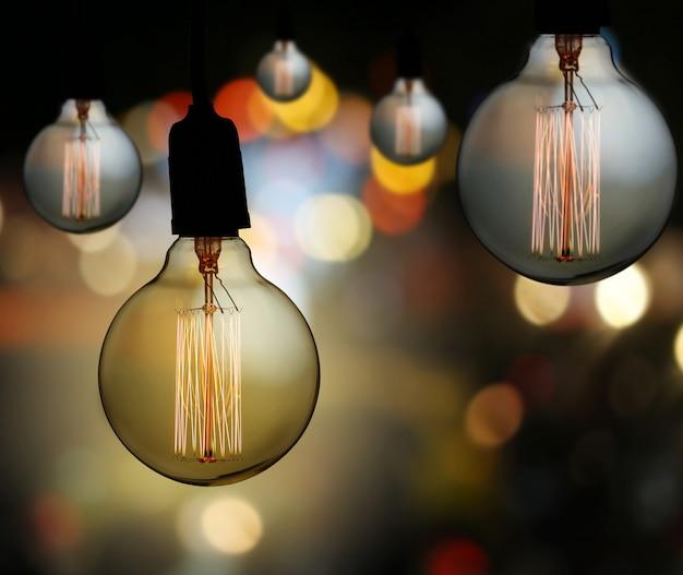 A lâmpada do vintage ou a ampola moderna penduram no teto no fundo do bokeh.