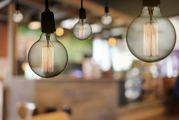 A lâmpada do vintage ou a ampola moderna penduram no teto no restaurante.