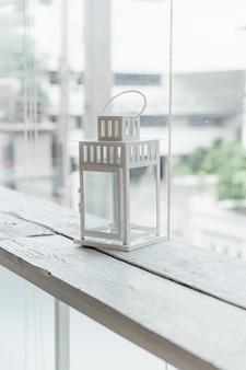 A lâmpada velha branca no branco pintou a tabela de madeira com janela de vidro e as árvores no fundo.