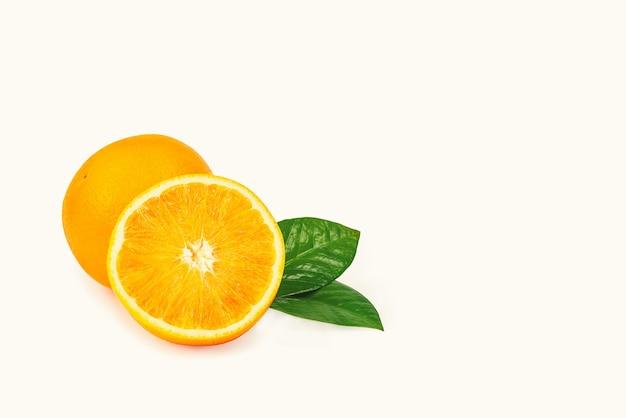 A laranja está isolada. fruta inteira e metade com folhas em um fundo branco. com uma sombra.
