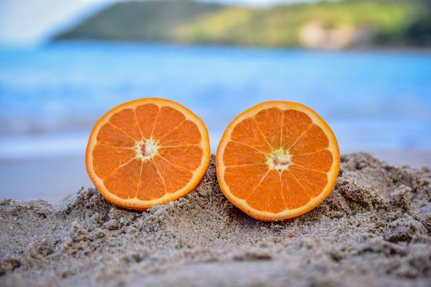 A laranja está no fundo da opinião do mar da praia, conceito das férias de verão