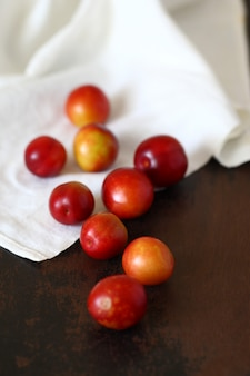 A laranja vermelha da fruta da ameixa espalhou na mesa marrom velha de madeira e na toalha de mesa amarrotada bege.