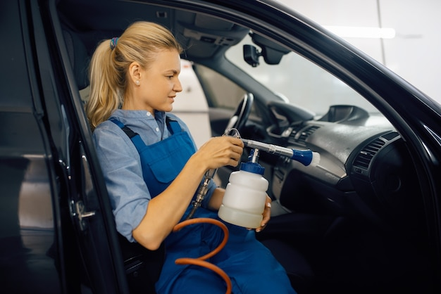 A lavadora feminina limpa o interior do automóvel, vista através do para-brisa, lava-carros. mulher lava veículo, estação de lavagem de carros, empresa de lavagem de carros