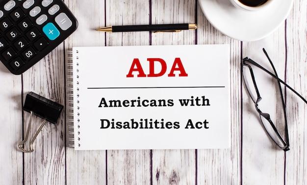 A lei dos americanos com deficiências da ada está escrita em um bloco de notas branco perto de uma calculadora, café, óculos e uma caneta