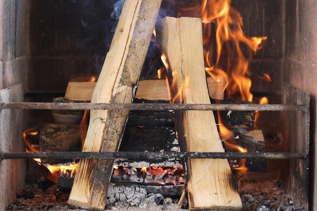 A lenha está queimando na lareira atrás da grade de metal, resfriamento sazonal e aquecimento em particular