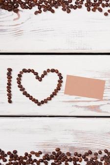 A letra i e a moldura do coração em forma de grãos de café com papel em branco. eu amo copyspace. espaço livre para texto.