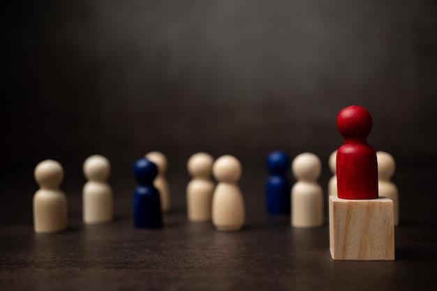 A liderança da figura de madeira em pé sobre a caixa mostra influência e empoderamento.