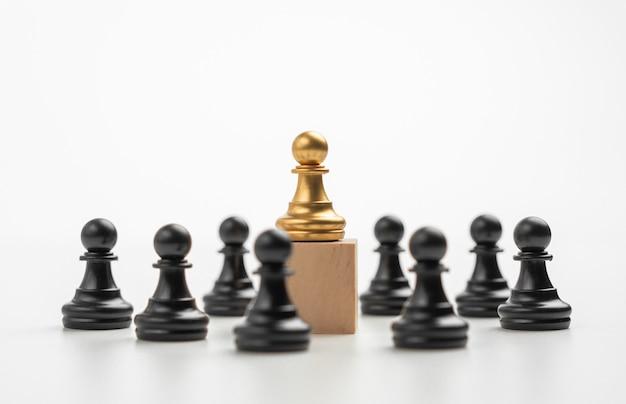 A liderança do peão do xadrez dourado em pé na caixa mostra influência e empoderamento