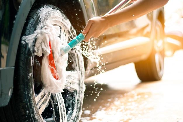 A liga do carro de lavagem do trabalhador do homem roda dentro o cuidado de carro.