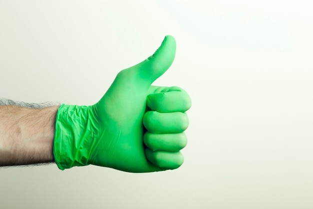«likeâ» numa luva médica. a mão do médico em uma luva médica verde sobre um fundo claro.