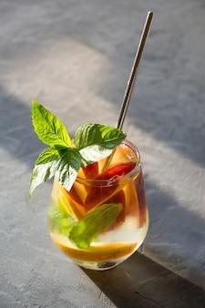 A limonada do pêssego do frescor no vidro decora a hortelã na luz de fundo. bebida saudável de verão. vertical.