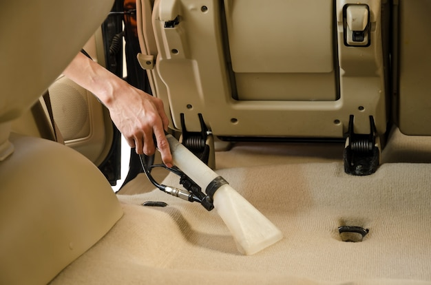 A limpeza profissional da parte traseira do interior assenta os carros modelo de suv do tapete
