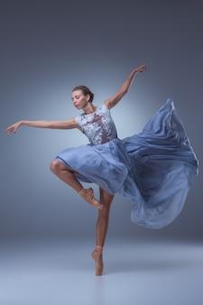A linda bailarina dançando em um vestido longo azul sobre fundo azul