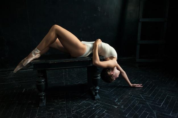 A linda bailarina posando no quarto escuro