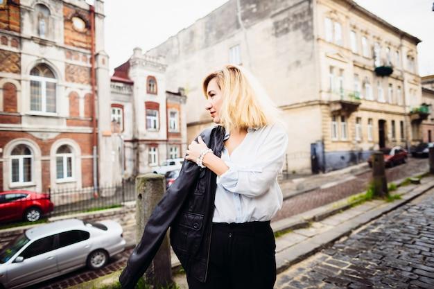 A linda dama mantendo uma jaqueta e de pé na rua
