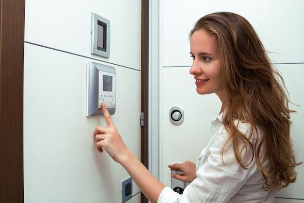 A linda garota abre a porta do apartamento usando vídeo porteiro ou sistema de interfone.