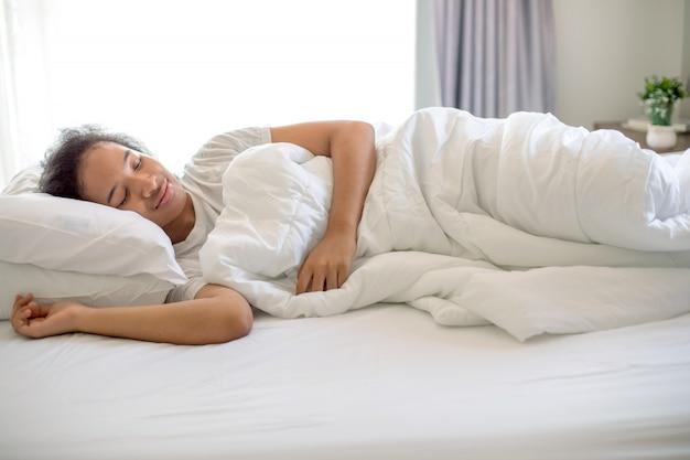 A linda garota americana dormir com sonho feliz na cama branca