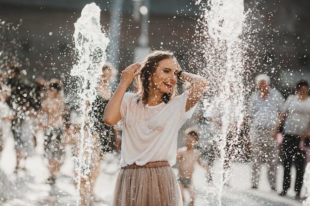 A linda garota andando perto da fonte