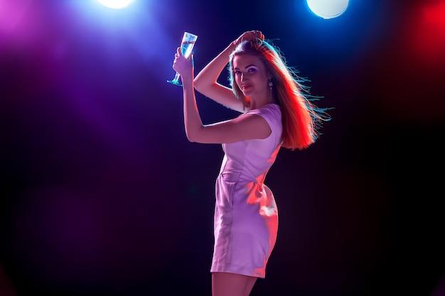 A linda garota dançando na festa bebendo champanhe