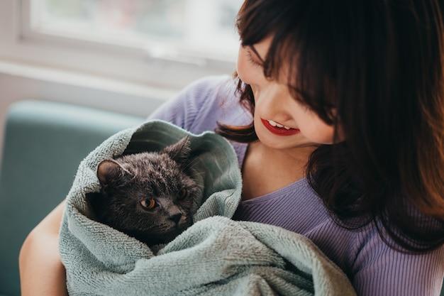 A linda garota estava secando o pelo de seu gato