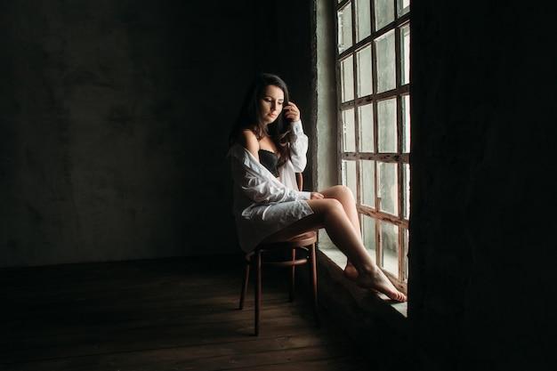 A linda garota se senta na cadeira perto da janela