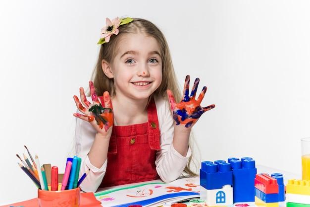 A linda garotinha com as mãos na pintura