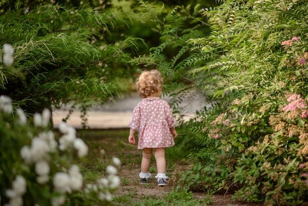 A linda garotinha com um cabelo loiro encaracolado em pé no parque em dia quente de verão