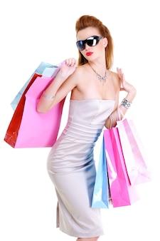 A linda jovem elegantemente vestida com compras nas mãos