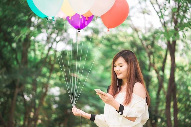 A linda mulher asiática está lendo mensagens de texto agradáveis no telefone celular enquanto está sentado no parque no morno dia de primavera, linda mulher ouvindo música em fones de ouvido e pesquisando informações em celular.